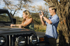 Tourist Couple Standing By Car Stock Photography