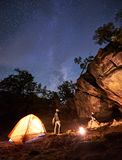 Tourist couple, standing at tent man and girl sitting on big boulder under dark starry sky. Camping night in valley amid huge rock formations. Young tourist stock photos