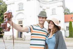 Tourist couple taking self portrait outside St. Casimir Church, Warsaw, Poland Royalty Free Stock Images