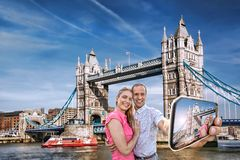 Tourist couple taking selfie against Tower Bridge in London, England, UK Royalty Free Stock Images
