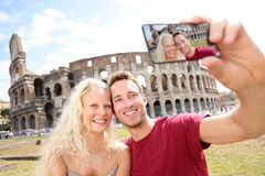 Tourist couple on travel in Rome by Coliseum. Tourist couple on travel taking pictures by Coliseum in Rome. Happy young romantic couple traveling in Italy Stock Photo