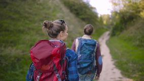 Tourist Couple Traveling, Walking In Nature. Tourist Couple Traveling, Walking With Backpacks On Summer Weekend, Enjoying Nature Of Mountains stock footage