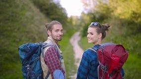 Tourist couple traveling, walking in nature. Tourist couple traveling, walking with backpacks on summer weekend, enjoying nature of mountains stock video