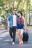 Tourist couple walking in city with suitcase Stock Images