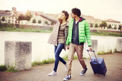 Tourist couple walking in city with suitecase Stock Images