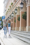 Tourist couple walking on sidewalk along building Royalty Free Stock Photos
