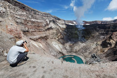 Tourist in crater active Gorely Volcano shoot of volcano acting fumarole and crater lake. Kamchatka Stock Image
