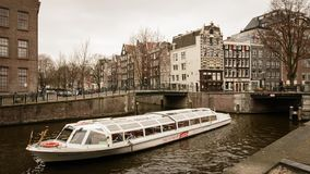 Tourist cruise boat in a canal in Amsterdam Netherlands. March, 2015. Landscape format stock photography