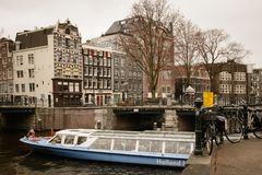 Tourist cruise boat in a canal in Amsterdam Netherlands. March, 2015. Landscape format royalty free stock photo