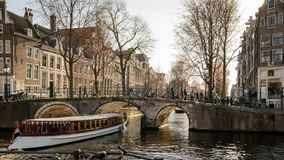 Tourist cruise boat in a canal in Amsterdam Netherlands. March, 2015. Landscape format stock image