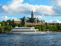 Tourist cruise boat floats on the blue water of the lake on the background of the beautiful buildings of Stockholm royalty free stock photography