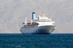 Tourist cruise sea liner is sailing in rocky bay Stock Images