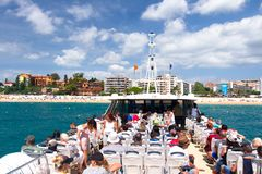 Tourist cruise on white boat to Lloret de Mar, Costa Brava, Spain. People swimming on boat to Tossa. Lloret de Mar, Costa Brava, Spain - august 26, 2018: Tourist stock image