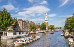 Tourist cruiseboat and historical tower in Amsterdam Stock Photo