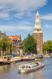 Tourist cruiseboat and historical tower in Amsterdam Royalty Free Stock Photos