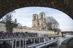 Tourist cruising boat in front the Notre Dame de Paris Stock Images
