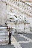 Tourist.Cute girl girl presents statue in capitoli Royalty Free Stock Images