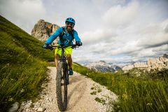 Tourist cycling in Cortina d`Ampezzo, stunning Cinque Torri and Royalty Free Stock Photos