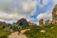 Tourist cycling in Cortina d`Ampezzo, stunning Cinque Torri and Stock Photos
