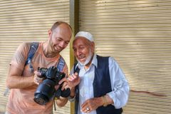 Tourist demonstrates photos for Iranians on camera display, Shir Stock Photos