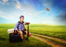 Tourist, der auf dem Gepäck in der Landschaft sitzt lizenzfreie stockfotos