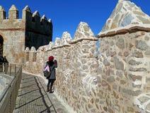 Tourist, der auf die mittelalterlichen Stadtmauern von Avila, Spanien wandert stockbilder