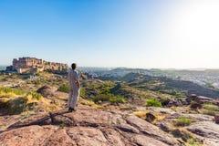 Tourist, der auf Felsen steht und die ausdehnende Ansicht von Jodhpur-Fort von oben, gehockt auf die Oberseite beherrscht die bla Lizenzfreie Stockbilder