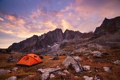 Tourist, der in den Bergen kampiert Lizenzfreies Stockbild