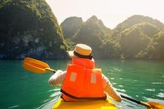 Tourist, der in der Halong-Buchtküste von Vietnam Kayak fährt stockfoto