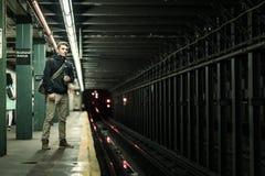 Tourist, der die Metro unter die Lichter in Brooklyn, New York wartet Lizenzfreie Stockbilder