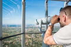 Tourist, der durch Teleskop schaut stockbild