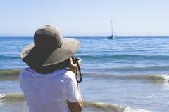Tourist, der ein Foto eines Bootes auf dem Strand macht Stockfotos