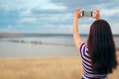 Tourist, der ein Smartphone-Foto der schönen natürlichen Ansicht macht Lizenzfreies Stockbild