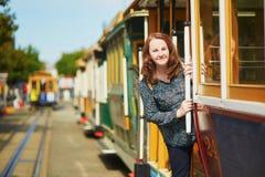 Tourist, der eine Fahrt in der berühmten Drahtseilbahn in San Francisco nimmt Stockbild