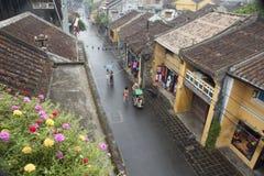 Tourist, der einen Ausflug nimmt, um alte Stadt Hoi Ans durch Zyklo an einem regnerischen Tag zu entdecken Stockfotografie