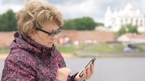 Tourist der erwachsenen Frau, der draußen einen Smartphone hält stock footage