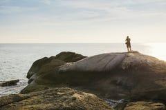 Tourist, der Fotos auf Felsen über dem Meer in Thailand macht stockfoto