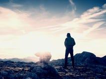 Tourist in der grünen Jacke an der Kieselpyramide auf scharfem Alpenstandpunkt Nationaler Alpenpark Lizenzfreies Stockfoto