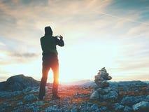 Tourist in der grünen Jacke an der Kieselpyramide auf scharfem Alpenstandpunkt Nationaler Alpenpark Lizenzfreies Stockbild