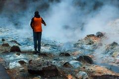 Tourist, der heißen Strom in Island aufpasst Stockfotografie