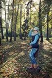 Tourist der jungen Frau, der in der Herbstnatur aufwirft Stockfotografie
