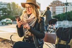 Tourist der jungen Frau mit dem Rucksack und Kamera, gekleidet im Hut und in den Gläsern, sitzt auf Bank in der Stadtstraße, benu Lizenzfreie Stockbilder