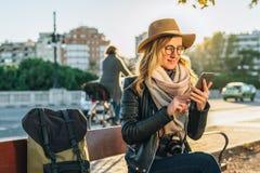 Tourist der jungen Frau mit dem Rucksack und Kamera, gekleidet im Hut und in den Gläsern, sitzt auf Bank in der Stadtstraße, benu Stockfotografie