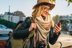 Tourist der jungen Frau mit dem Rucksack und Kamera, gekleidet im Hut und in den Gläsern, sitzt auf Bank in der Stadtstraße, benu Lizenzfreie Stockfotografie