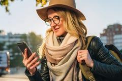 Tourist der jungen Frau mit dem Rucksack und Kamera, gekleidet im Hut und in den Gläsern, sitzt auf Bank in der Stadtstraße, benu Stockbild