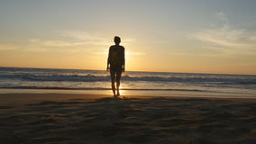 Tourist der jungen Frau mit Rucksack gehend auf Strand zum Ozean am Sonnenuntergang und an angehobenen Händen Mädchenwanderer, de stock video