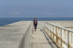 Tourist, der mit einem Hund auf einer Hafenstruktur geht stockfoto