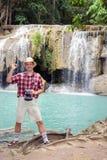 Tourist, der neben Wasserfall aufwirft Lizenzfreies Stockbild