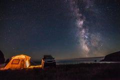 Tourist, der an der Seeküste nachts mit Milchstraße kampiert Lizenzfreie Stockfotografie