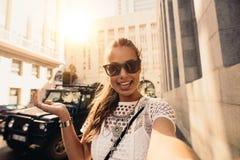 Tourist, der selfie in einer Straße umgeben durch Gebäude nimmt Lizenzfreies Stockbild